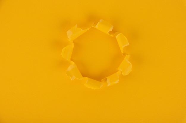 Uma folha de papel amarela com um furo no meio. fundo, textura. copie o espaço.