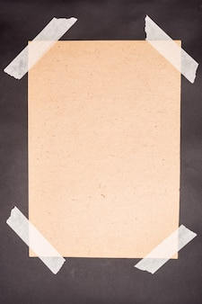 Uma folha de papel artesanal colada com fita adesiva branca em um fundo preto