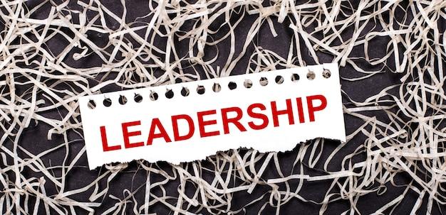 Uma folha de papel branca com o texto liderança repousa sobre aparas brancas em um fundo escuro