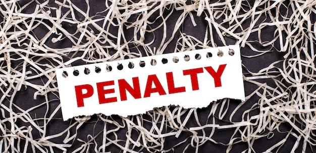 Uma folha de papel branca com o texto penalidade repousa sobre aparas brancas em um fundo escuro.