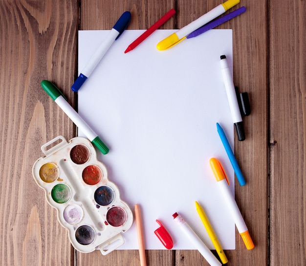 Uma folha de papel branca estava sobre uma mesa de madeira, perto, lápis, tintas e marcadores.