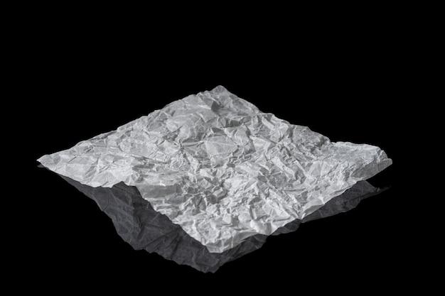 Uma folha de papel branco amassado sobre uma superfície preta espelhada. um pedaço isolado de pergaminho.