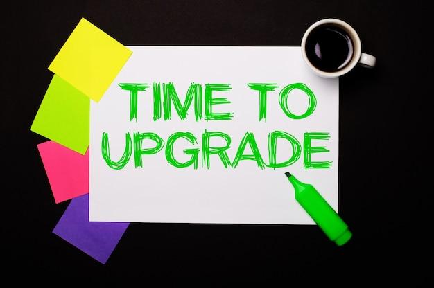 Uma folha de papel com a inscrição time to upgrade, uma xícara de café, adesivos coloridos brilhantes para anotações e um marcador verde em uma parede preta. vista de cima.