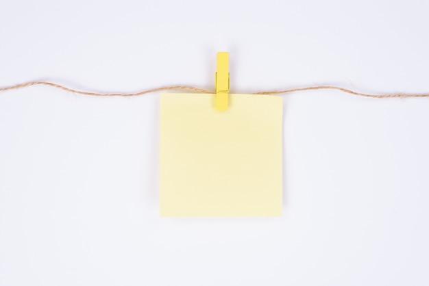 Uma folha de papel com lugar para texto pendurado em uma corda anexa com pings de design isolado de fundo branco