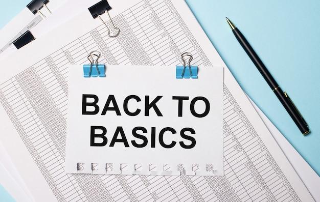 Uma folha de papel com o texto de volta ao básico está sobre os documentos perto da caneta em uma superfície azul clara