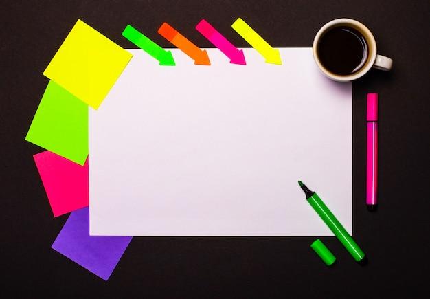 Uma folha de papel com um local para inserir texto ou ilustrações, uma xícara de café, adesivos multicoloridos brilhantes para anotações e marcadores verdes e rosa em uma parede preta. vista superior com espaço de cópia.