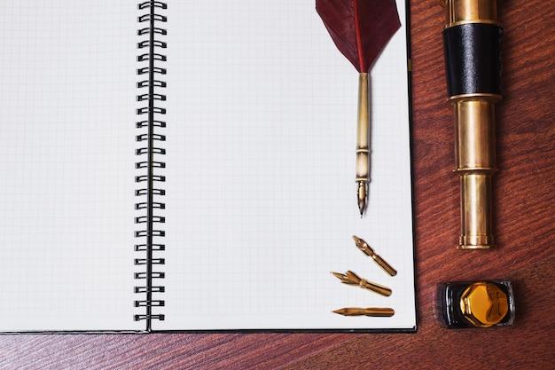 Uma folha de papel de caderno, caneta-tinteiro e tinta, luneta em fundo de madeira, copyspace