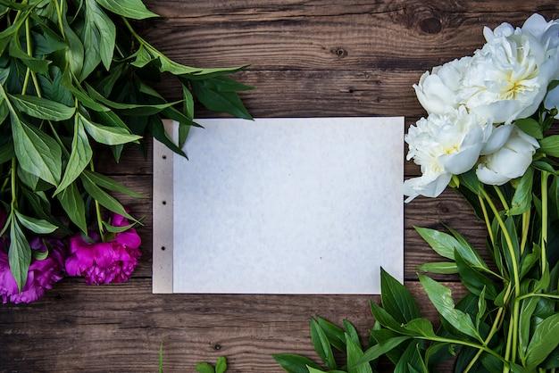 Uma folha de papel e algumas peônias brancas e rosa em madeira com espaço de cópia como um cartão postal