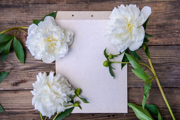 Uma folha de papel e três peônias brancas sobre um fundo de madeira