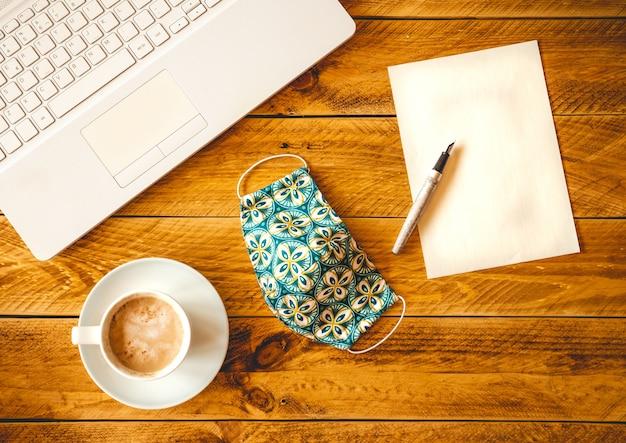 Uma folha de papel em branco com uma caneta sobre uma mesa de madeira com uma xícara de café e máscara protetora.