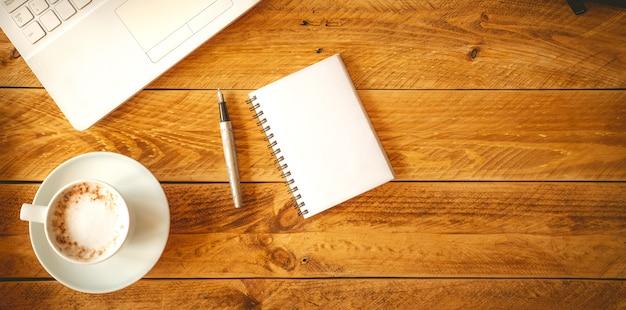 Uma folha de papel em branco com uma caneta sobre uma mesa de madeira com uma xícara de café.