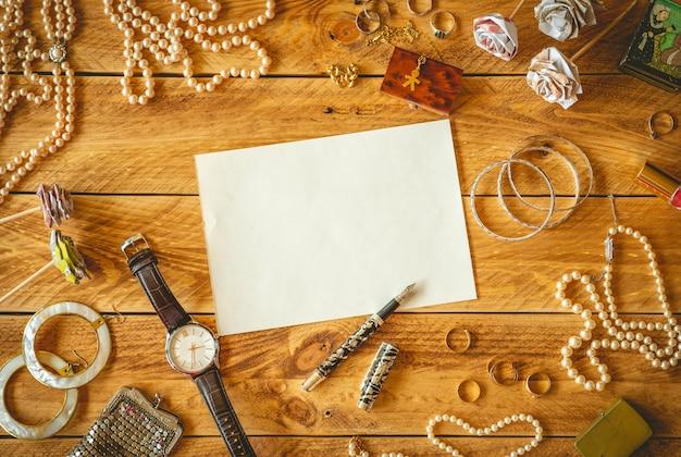 Uma folha de papel em branco para escrever uma carta em uma mesa de madeira com algumas memórias e joias