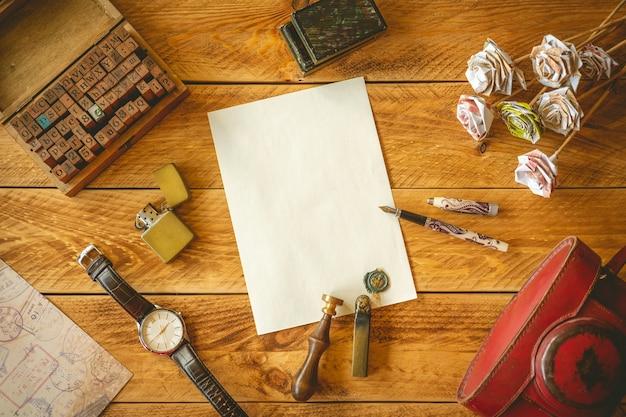 Uma folha de papel em branco para escrever uma carta em uma mesa de madeira com algumas memórias