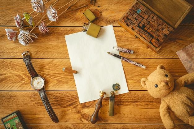 Uma folha de papel em branco para escrever uma carta sobre uma mesa de madeira com algumas memórias