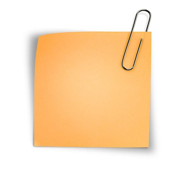 Uma folha de papel laranja em um clipe de papel em um fundo branco isolado