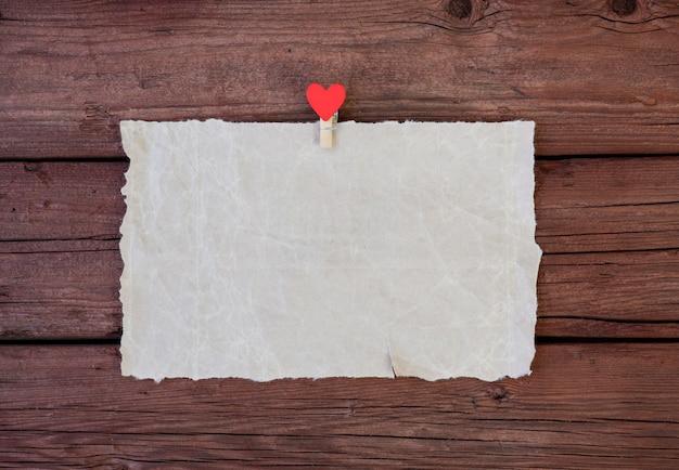 Uma folha de papel pergaminho com um prendedor de roupa com um coração vermelho em um fundo de madeira. copie o espaço