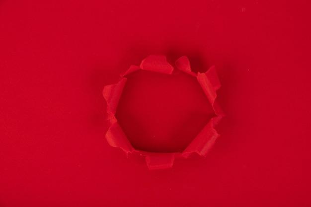 Uma folha de papel vermelha com um furo no meio. lembrete. fundo, textura. copie o espaço. Foto Premium