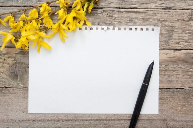 Uma folha em branco do bloco de notas para anotações. galhos de primavera e caneta. zombar de texto