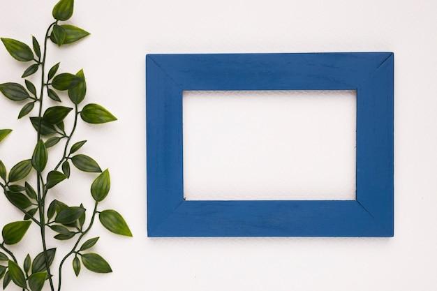 Uma folhas artificiais perto do quadro de madeira azul isolado no fundo branco
