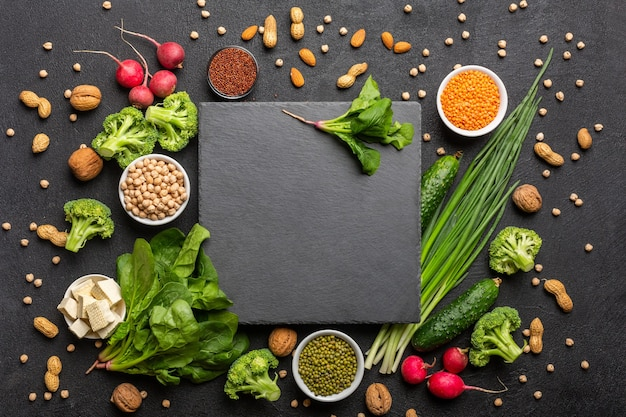Uma fonte de proteína para vegetarianos. alimentos saudáveis e limpos: verduras, legumes, nozes e leguminosas, vista superior em um fundo preto com uma pedra de corte preta no centro.