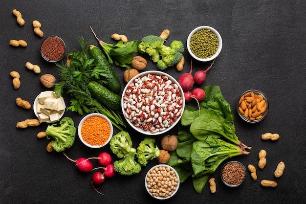 Uma fonte de proteína para vegetarianos: vegetais, nozes, sementes e leguminosas, vista superior em um fundo preto. conceito: compre alimentos saudáveis e limpos.