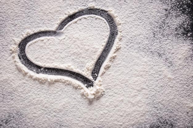 Uma forma de coração desenhada na farinha em um fundo preto. fechar-se.