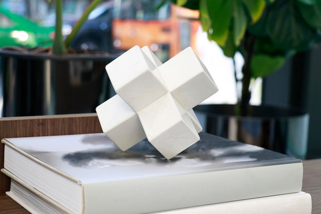 Uma forma poligonal de cerâmica branca colocada no livro na sala de estar para decoração