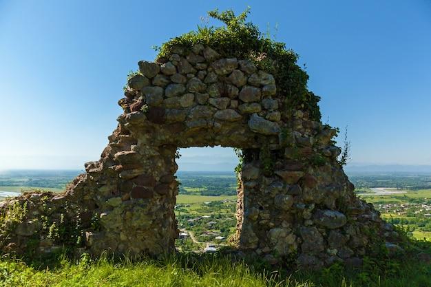 Uma fortaleza abandonada nas montanhas coberta de grama contra o fundo das montanhas