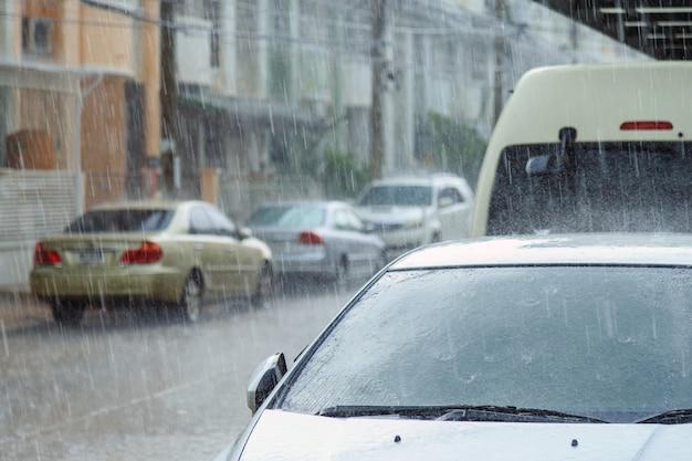 Uma forte chuva caindo sobre um estacionamento de carros em frente a uma casa em um dia chuvoso.