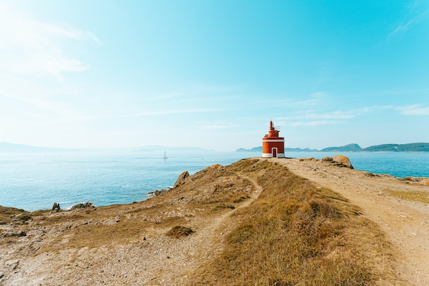 Uma foto colorida de um farol vermelho na frente do oceano com ilhas no horizonte e espaço de cópia