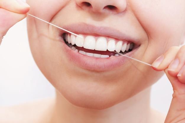 Uma foto cortada de uma bela jovem passando fio dental em um fundo branco