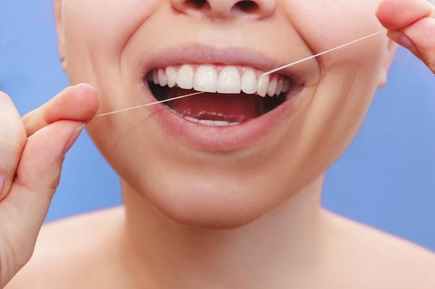 Uma foto cortada de uma bela jovem passando fio dental em uma parede azul
