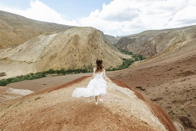 Uma foto da noiva de uma mulher na parte de trás em um vestido de noiva branco correndo em uma montanha selvagem. viagem de casamento e conceito de férias de lua de mel