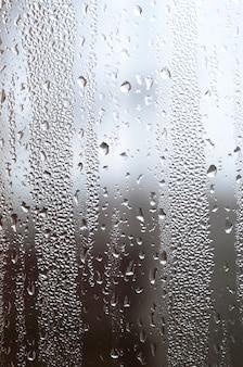 Uma foto da superfície de vidro da janela, coberta com uma infinidade de gotículas de vários tamanhos.