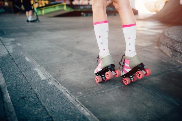 Uma foto das pernas da garota em rolos. ela está patinando na estrada. também ela está posando e em pé na ponta dos pés.