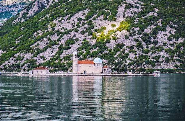 Uma foto de alto ângulo de uma península no mar com uma cordilheira ao fundo da igreja de nossa ...
