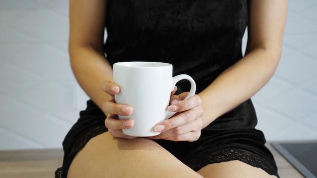 Uma foto de close da mulher segurando um copo branco na mão na cozinha