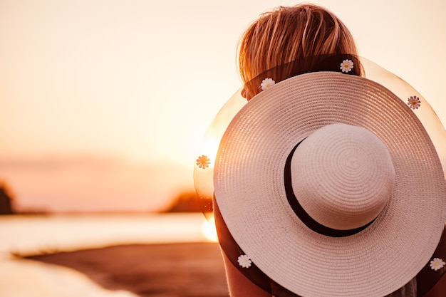 Uma foto de close de uma mulher ao pôr do sol, uma jovem loira bonita com um chapéu de palha branco decorado com ...