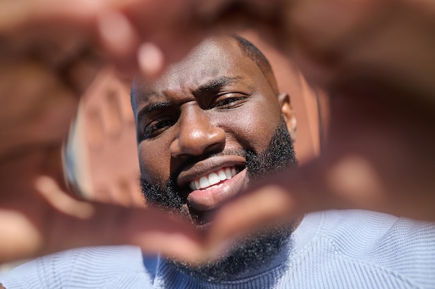 Uma foto de close-up de um homem barbudo de pele escura