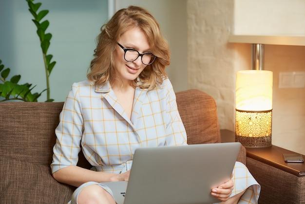 Uma foto de close-up de uma mulher de óculos funciona remotamente em um laptop em seu apartamento. uma garota bonita durante uma videoconferência com seus parceiros em casa.