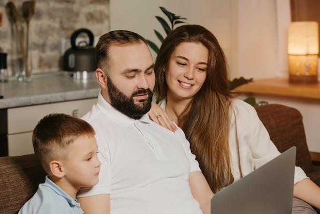 Uma foto de close-up do pai com barba mostrando suas conquistas no trabalho em um laptop para o filho e a esposa sorridente em casa