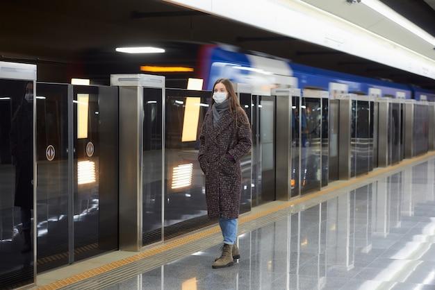 Uma foto de corpo inteiro de uma mulher com uma máscara facial de médico esperando a chegada de um trem na plataforma do metrô
