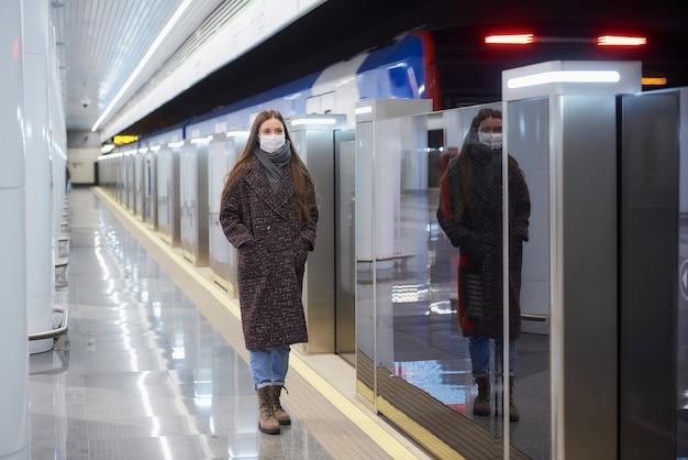 Uma foto de corpo inteiro de uma mulher com uma máscara médica em pé perto do trem que parte na plataforma do metrô