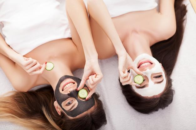 Uma foto de duas amigas relaxantes com máscaras faciais