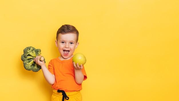 Uma foto de estúdio de um menino segurando um brócolis fresco e uma maçã verde.