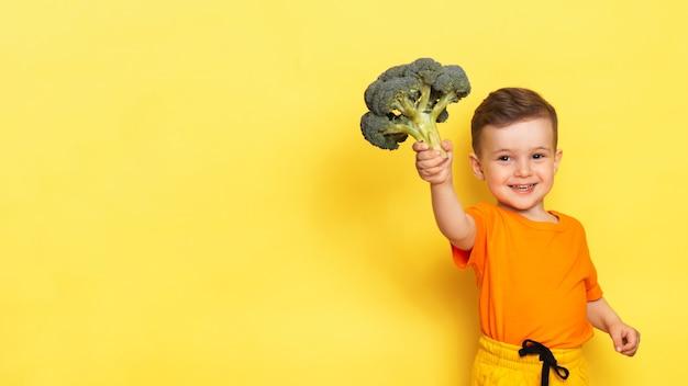Uma foto de estúdio de um menino segurando um brócolis fresco.