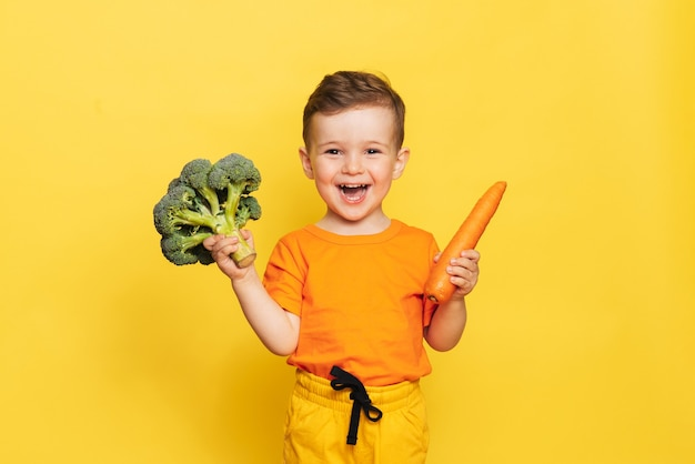 Uma foto de estúdio de um menino sorridente segurando brócolis fresco e cenoura em uma parede amarela.