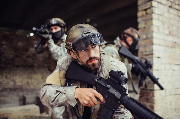 Uma foto de guerreiros do lado de fora. eles estão segurando rifles e guardando um ao outro. os homens são muito cuidadosos. eles estão no campo de batalha.