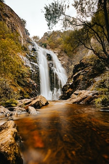 Uma foto de longa exposição de uma enorme cachoeira no meio da floresta durante o outono