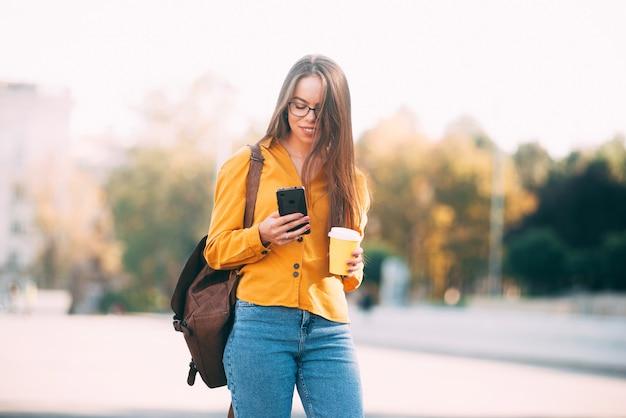 Uma foto de mulher com um copo de bebida quente na mão e segurando um telefone, está andando por uma cidade